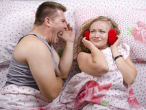 The guy is yelling at the girl lying in bed Royalty Free Stock Image
