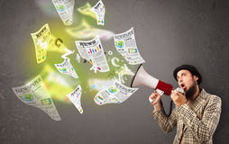 Guy yelling into loudspeaker and newspapers fly out Stock Images