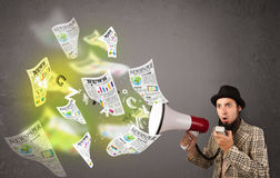 Guy yelling into loudspeaker and newspapers fly out Royalty Free Stock Images