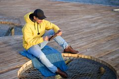 Guy in the yellow jacket and black cap sitting on the pier with a tablet stock images