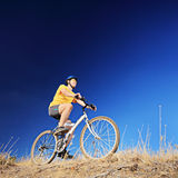 A guy with yellow shirt and helmet riding a mountain bike Royalty Free Stock Image