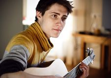 Guy in yellow sweater plays acoustic guitar while sitting at home. A handsome young brown-eyed guy with dark hair in a yellow-gray sweater plays an acoustic royalty free stock images