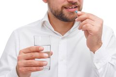A guy is holding a glass of water and is about to drink a capsule in his hand close-up on a white isolated background stock photo