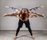 Guy and young woman doing strength exercises in yoga assanes. Acroyoga concept. Guy and young women doing strength exercises in yoga assanes. Acroyoga concept Royalty Free Stock Image