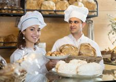 Guy and young woman offering and selling fresh buns. Guy and young women offering and selling fresh buns loaves cookies croissants baguettes from disply and Royalty Free Stock Photography
