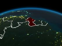 Guyana on Earth at night. Space orbit view of Guyana highlighted in red on planet Earth at night with visible country borders and city lights. 3D illustration Stock Images