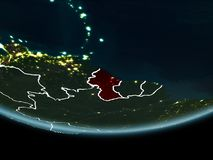 Guyana on Earth from space at night. Guyana highlighted in red on planet Earth at night with visible borders and city lights. 3D illustration. Elements of this Stock Photo