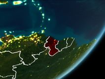 Guyana on night Earth. Guyana as seen from Earth's orbit on planet Earth at night highlighted in red with visible borders and city lights. 3D illustration Stock Photography