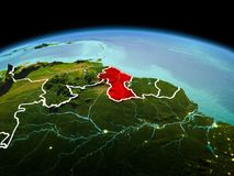 Guyana on planet Earth in space. Morning above Guyana highlighted in red on model of planet Earth in space with visible border lines and city lights. 3D Stock Photo