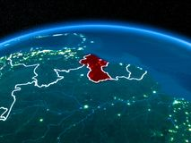 Guyana from space at night. Orbit view of Guyana highlighted in red with visible borderlines and city lights on planet Earth at night. 3D illustration. Elements Stock Photo