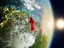 Guyana during sunrise. Highlighted in red on planet Earth with visible country borders. 3D illustration. Elements of this image furnished by NASA Stock Photos