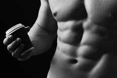 Guys abs and strong chest. Athletes body in close up, hand holding coffee cup. Copy space. Male with naked torso isolated on black background. Sports, ad royalty free stock photography