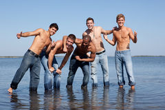 Guys at the beach. 5 men in jeans at the beach, standing in the water Royalty Free Stock Photo