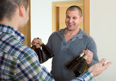 Guys with beer bottles at doorway Royalty Free Stock Image