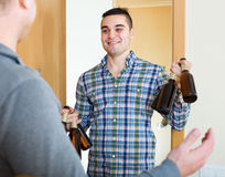 Guys with beer bottles at doorway Royalty Free Stock Images