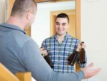 Guys with beer bottles at doorway Stock Photo