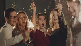 Guys celebrating by waving fireworks, enjoying party on New Years or Christmas Eve. Close up portrait friends holding