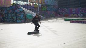 The guys does tricks on a skateboard in a skate park painted with graffiti stock video