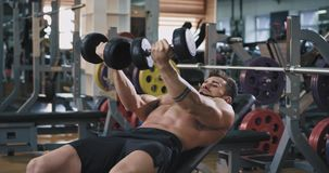 A guys is doing heavy workouts with his dung bell weights he looks very handsome and concentrated on his abs workout. A guys is doing heavy workouts with his stock video footage