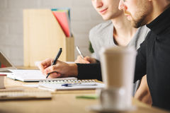 Guys doing paperwork. Portrait of handsome young guys doing paperwork in modern office with blurry coffee cup and other items. Teamwork concept royalty free stock photos