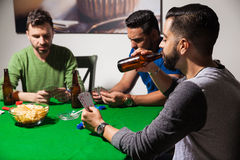 Guys drinking beer on poker night. Group of friends playing cards and hanging out at home while enjoying some beer and snacks Stock Photos
