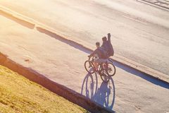 Guys with fishing rods on bicycles in the sun. For any purpose Royalty Free Stock Image