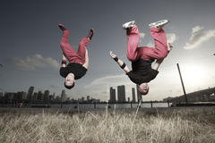 Guys flipping. Pair of acrobatic guys flipping in mid-air royalty free stock photo