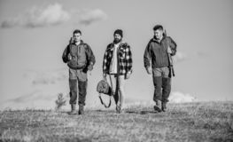 Guys gathered for hunting. Men carry hunting rifles. Hunters with guns walk sunny fall day. Hunting as hobby and leisure. Brutal hobby. Group men hunters or royalty free stock image