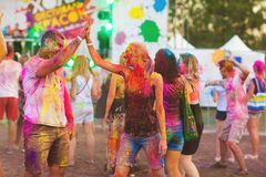 Guys with a girl celebrate holi festival. Fun on holiday stock images
