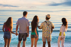 Guys and girls admire the view of the sea. Stock Images
