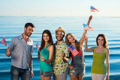 Guys and girls with American flags on the beach. Patriots of America. Young people having fun Royalty Free Stock Images