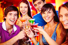 Guys and girls toasting. Group of young friends with cocktails looking at camera at party stock image