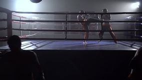 Guys in gloves beats a pear, in the background in the ring there is a sparring of kickboxers . Slow motion