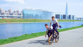 The guys have fun in nature, cling to each other, skate, bike. Saint-Petersburg. Russia. 17.05.2018 royalty free stock photography
