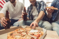 Guys having fun. Attractive guys are drinking beer, eating pizza, talking and smiling while resting at home royalty free stock images