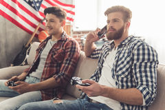 Guys at home. Attractive guys are playing video games and smiling while sitting on couch at home. One men is talking on the mobile phone royalty free stock image