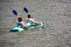 Guys on a kayak paddling Royalty Free Stock Image