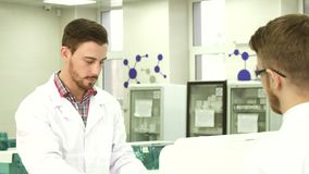 One lab technician hands over test tubes to his colleague for researches. The guys are in the lab. One of them gives the second stand with test tubes. The stock footage