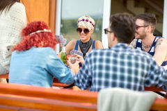 Guys and lassies in restaurant outdoor play cards and drink. Guys and lassies in nice spring day in restaurant outdoor play cards, drinks beer and makes joke Royalty Free Stock Image