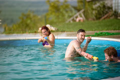 Guys and lassies spraying each other with water guns in pool. Guys and lassies having fun when spraying each other in open pool at summer Royalty Free Stock Image