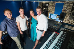Guys musician and a girl singer in the Recording Studio. Three smiling guys musician and a girl singer in the Recording Studio with equipment, with property Stock Photography