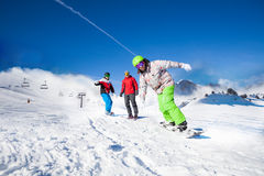 Guys and one man snowboarding downhill Stock Images