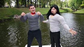 Guys performers wearing fake muscle shirt dance and sing in floating boat