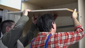 Guys place the shelf into the wardrobe. Two men are assembling new furniture in freshly painted room. They use compact cordless drill-driver, hammer and various stock video