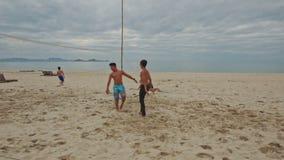 Guys Play Beach Volleyball on Large Sand Beach. NHA TRANG, KHANH HOA/VIETNAM - JUNE 26 2016: Local guys play beach volleyball on large sand beach against ocean stock video footage