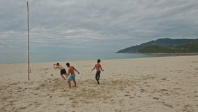 Guys Play Beach Volleyball on Large Sand Beach. NHA TRANG, KHANH HOA/VIETNAM - JUNE 26 2016: Local guys play beach volleyball on large sand beach against ocean stock footage