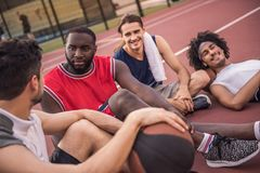 Guys playing basketball. Handsome basketball players are talking and smiling while sitting on basketball court outdoors after the game Stock Image
