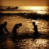 Guys playing in beautiful beach water. Sunset time silhouettes of guys playing on waves and backlighting Royalty Free Stock Image