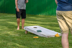 Guys playing cornhole game outside on sunny day stock photography