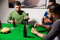 Guys playing dice on poker night Stock Image